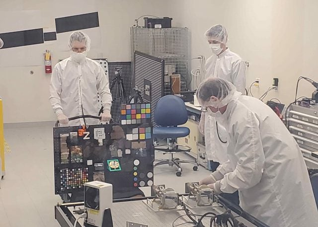 """Members of the Mars 2020 Perseverance rover Mastcam-Z calibration group in the clean room setting up the """"GeoBoard"""" rock and standards target for imaging by the flight cameras at Malin Space Science Systems in May, 2019."""
