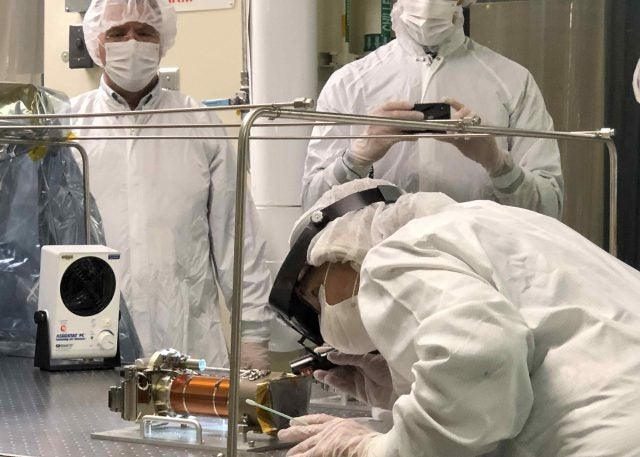 A JPL technician carefully inspects one of the flight Mastcam-Z cameras after it was officially delivered from the team to the rover in May 2019.
