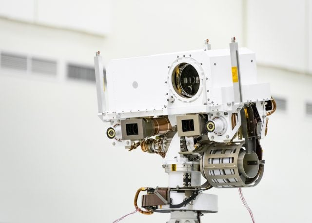 This image, taken in the Spacecraft Assembly Facility's High Bay 1 at the Jet Propulsion Laboratory in Pasadena, California, on July 23, 2019, shows a close-up of the head of Mars 2020's remote sensing mast. The mast head contains the SuperCam instrument (its lens is in the large circular opening). In the gray boxes beneath mast head are the two Mastcam-Z imagers. On the exterior sides of those imagers are the rover's two navigation cameras.