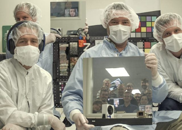 A photo taken by one of the flight cameras shows, left to right: Andy Winhold, Justin Maki, Jim Bell and Alex Hayes. Bell is holding a mirror reflecting the faces of additional team members looking into the cleanroom window from the data analysis room outside.